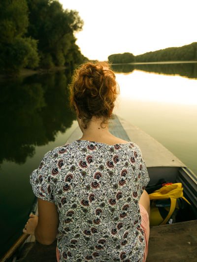Rear view of woman riding a boat on a lake against sky