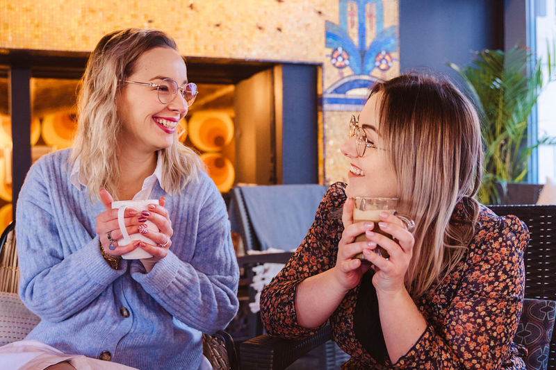Smiling friends holding coffee talking while sitting in restaurant