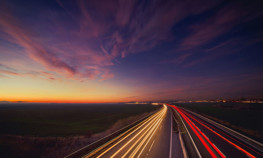 Light trails on highway at sunset