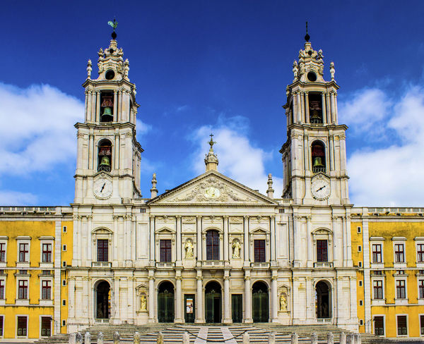 Front of the Royal Palace of Mafra Architecture Blue Building Exterior Built Structure Cathedral Church Clock Clock Tower Cloud Cloud - Sky Day Façade Low Angle View No People Outdoors Place Of Worship Religion Sky Spirituality Tourism Tourism In Portugal Travel Destinations