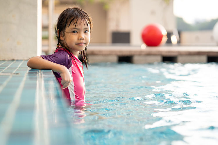 Ball Child Childhood Cute Day Females Girls Innocence Leisure Activity Lifestyles One Person Pool Real People Selective Focus Swimming Pool Water Women
