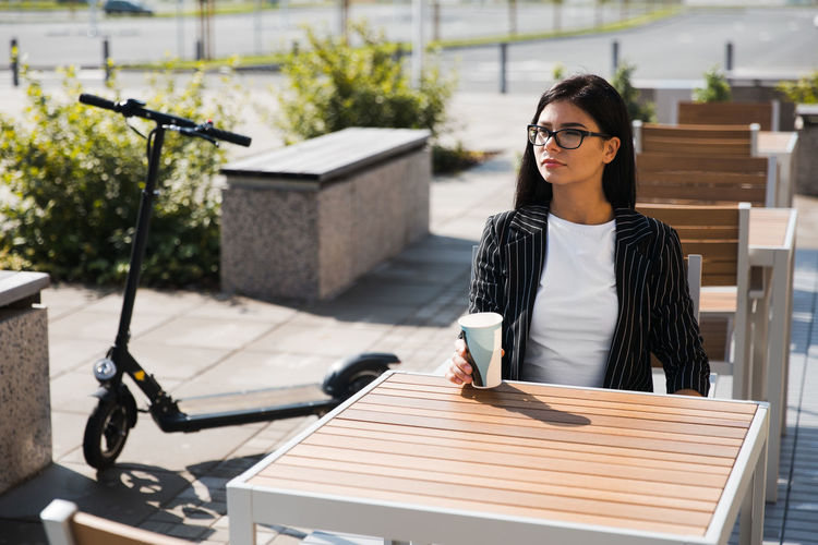 Young woman holding disposable cup while sitting at table