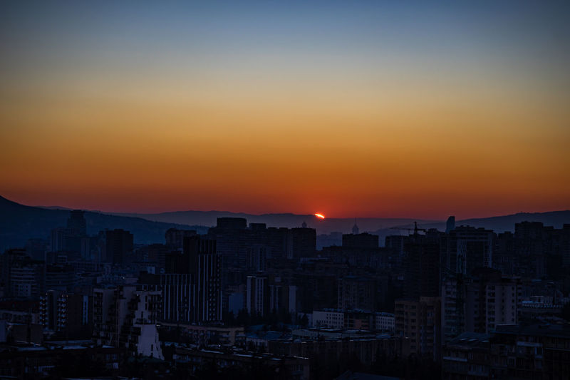 Sunrise time over tbilisi's downtown with bright blue sky and red sun