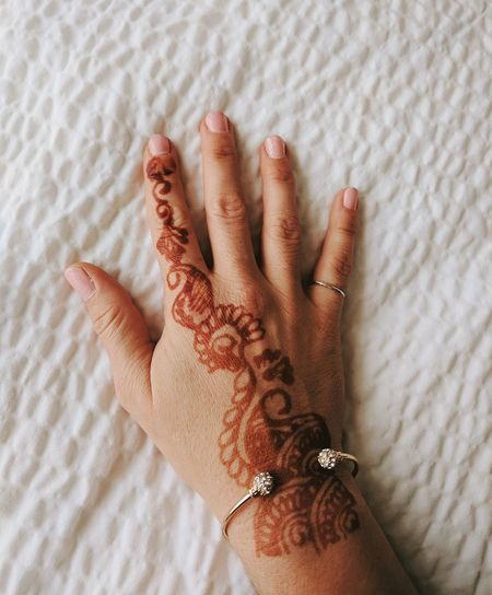 Cropped hand of woman with henna tattoo on bed