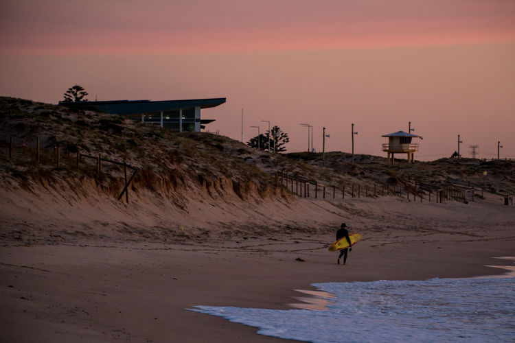 Surfer walking at beach against sky during sunset