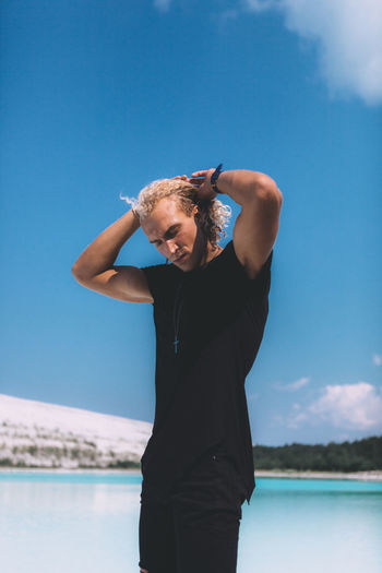 Blond curly man is standing on the stone at the crystal clear lake. Trendy hairstyle. Awesome the weather, blue sky. Summer time. Adult Blue Day Front View Hands Behind Head Leisure Activity Lifestyles Nature One Person Outdoors Real People Sea Sky Standing Sunlight Three Quarter Length Water Young Adult Young Men