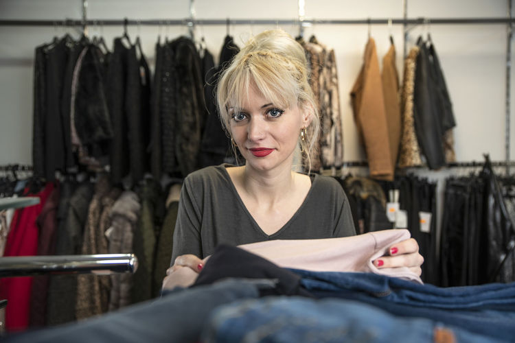 Entrepreneur Boutique Customer  Front View Young Adult Business Smiling Small Business Choice Indoors  One Person Rack Store Retail  Shopping Fashion Clothing Consumerism Hairstyle Adult Women Folding Clothes Working Work Blondy Girl