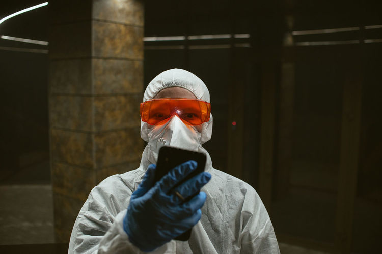 Portrait of man with smart phone wearing protective workwear