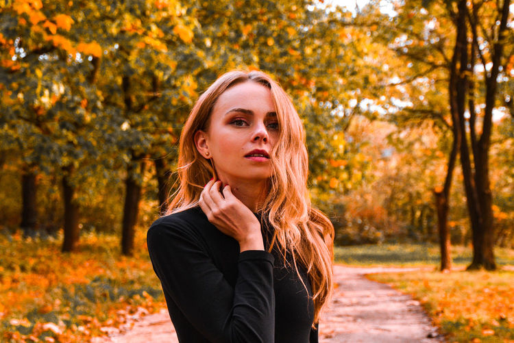 Portrait of young woman with blonde hair in autumn golden park. autumn concept. fall leaves