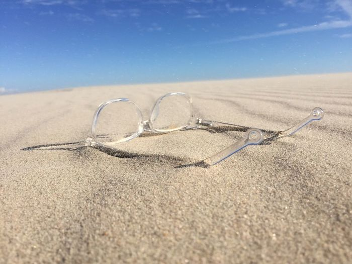 Clear Glasses On Sand At Beach