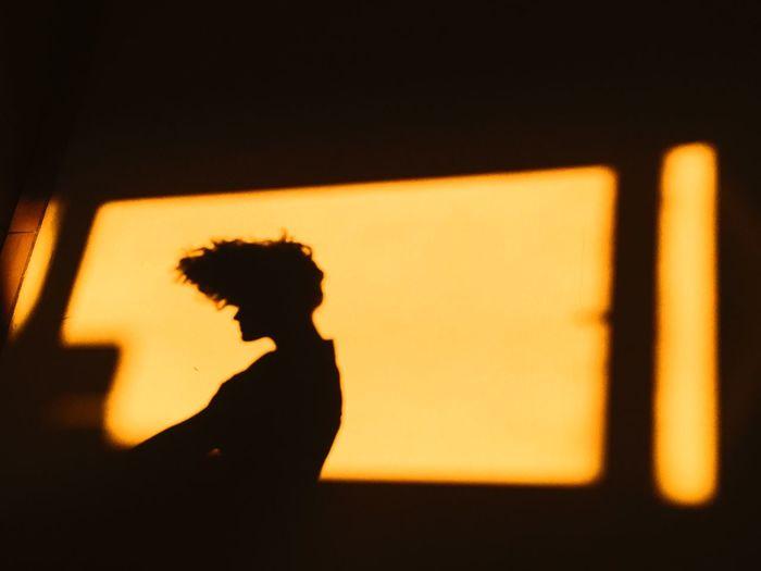 Silhouette man sitting by window against orange sky