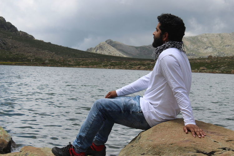 Man sitting on rock looking at view of mountains