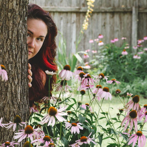 Beauty In Nature Blooming Day Echinacea Face Flowers Focus On Foreground Long Hair Looking At Camera Nature One Person Outdoors Part Of Body Pastel Colors Person In Nature Pink Flowers Plants Portrait Tree Trunk Upper Body Woman