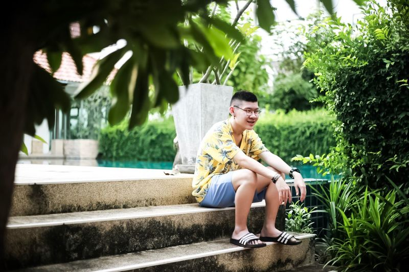 Smiling Teenage Boy Sitting On Staircase By Plants
