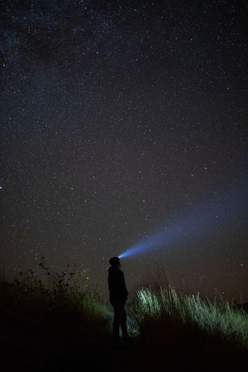 Woman with flashlight standing against star field
