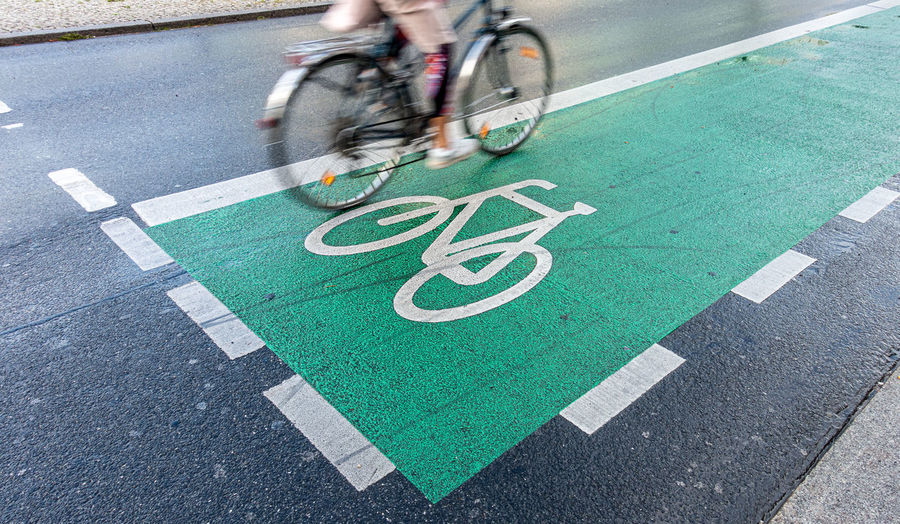 Low section of man riding bicycle on road