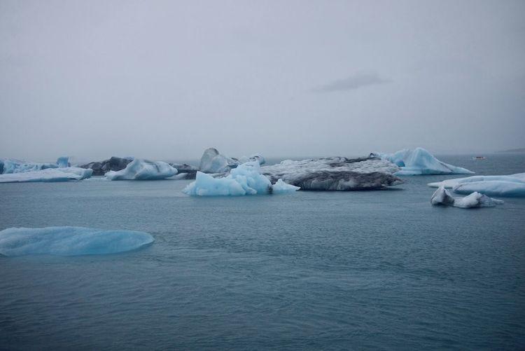 Scenic view of frozen iceberg against sky