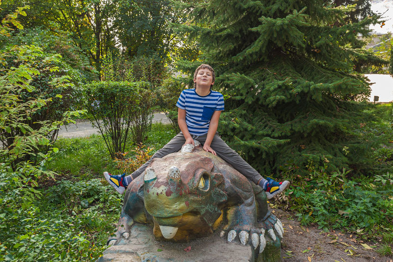 Cheerful smiling boy in a striped t-shirt sits on a dinosaur statue in the park at the playground