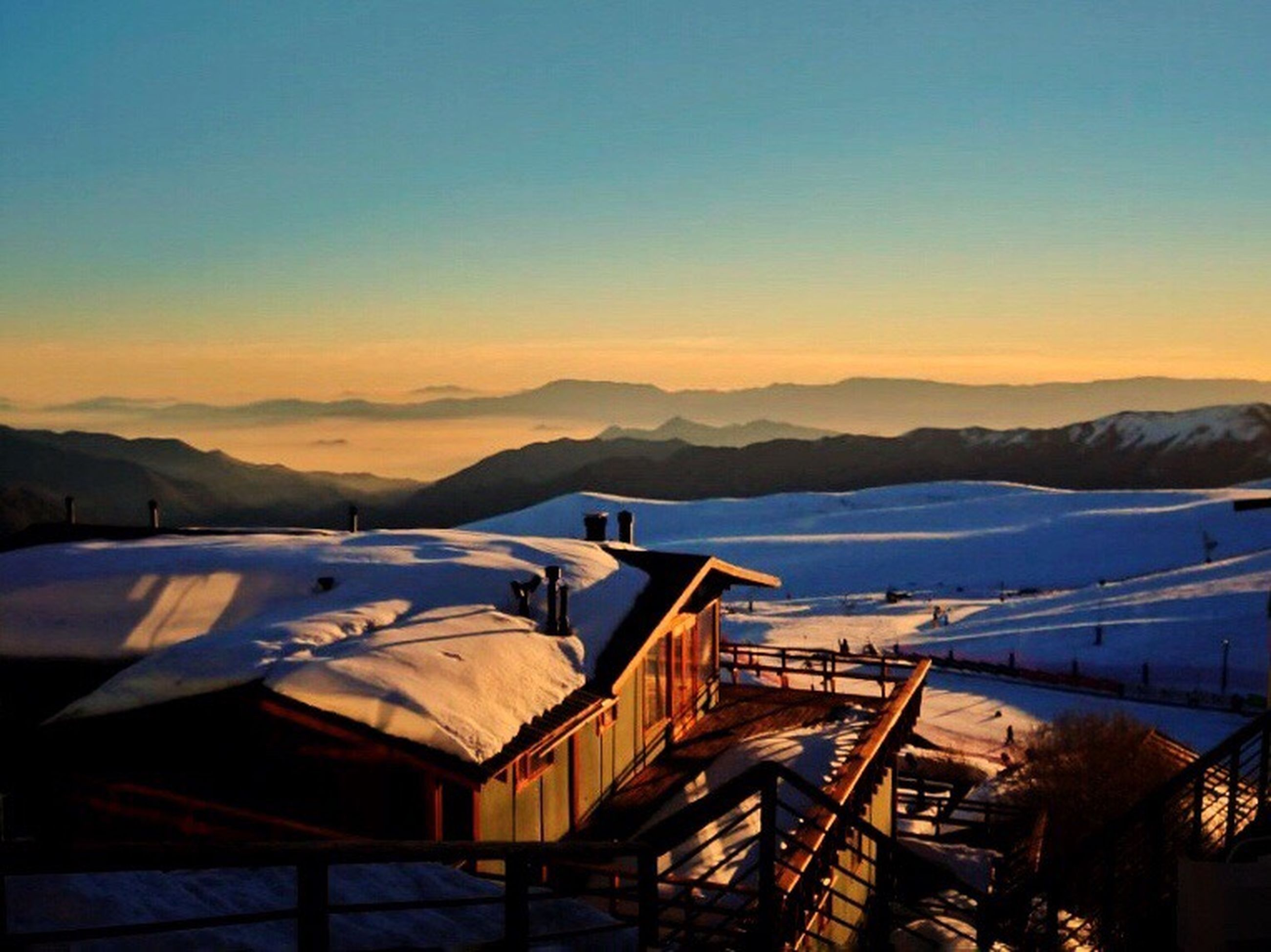 mountain, sunset, snow, winter, cold temperature, no people, nature, mountain range, outdoors, clear sky, scenics, tranquil scene, built structure, transportation, sky, tranquility, beauty in nature, roof, sunlight, architecture, building exterior, landscape, day