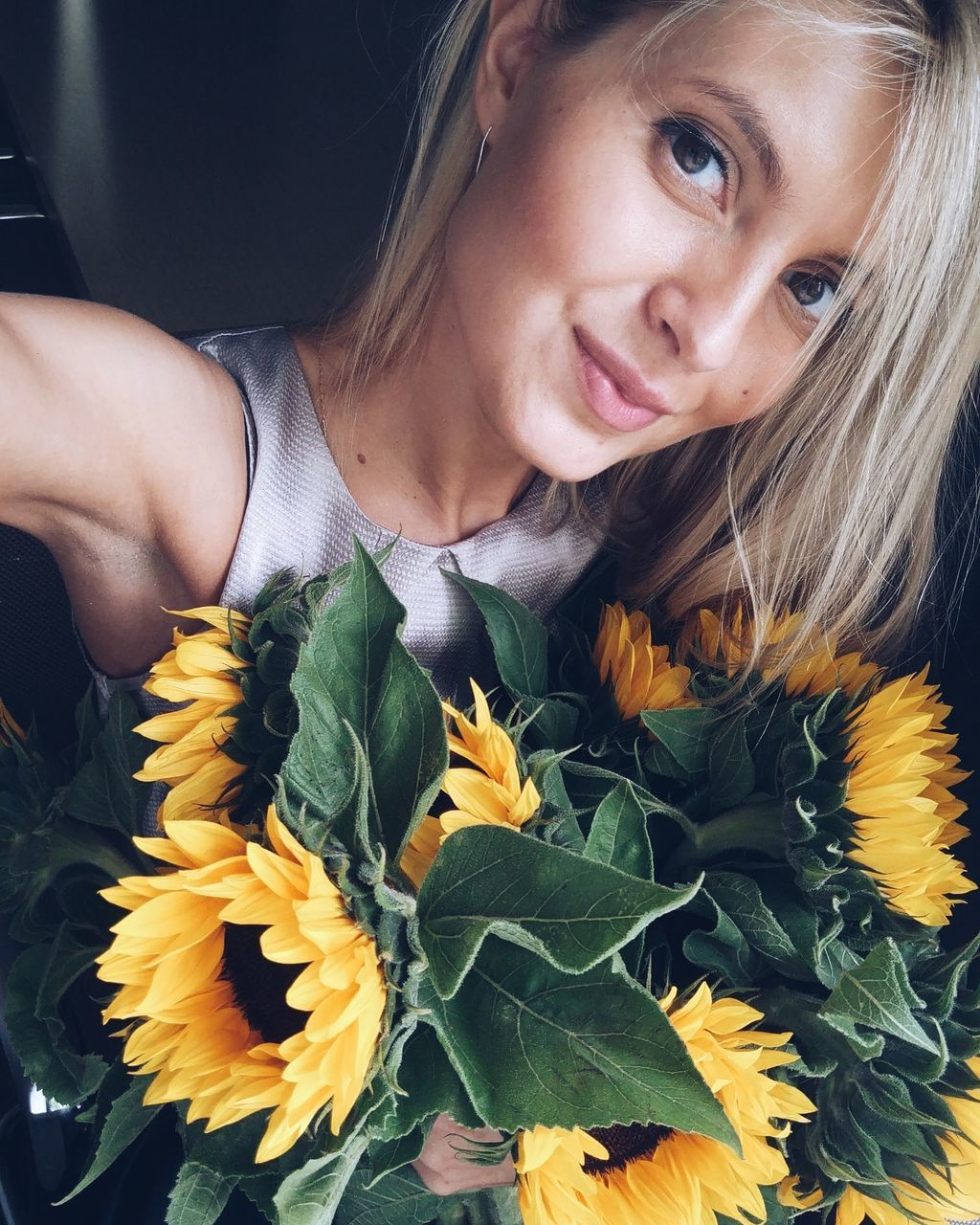Portrait Of Woman With Sunflowers Traveling In Car