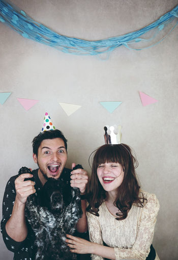 Cheerful couple with dog by wall during celebration