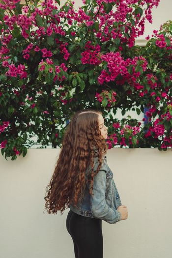 Side view of teenage girl standing by wall
