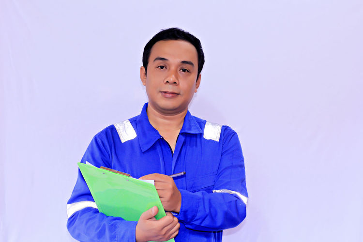 Portrait of a young Asian Engineer with a clipboard looks and checking - goods concept Front View Portrait Looking At Camera Smiling Studio Shot One Person Standing Men Copy Space Holding Blue Indoors  Young Adult