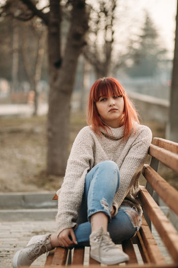 Tree Sitting Casual Clothing One Person Leisure Activity Focus On Foreground Young Adult Redhead Day Hairstyle Three Quarter Length Emotion Women Smiling Looking Nature Young Women Hair Jeans Outdoors Scarf