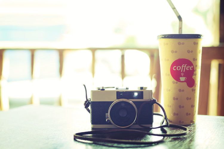 Retro camera with coffee in cafe - vintage filter effect Camera Coffee Coffee Shop Drinks Tourist Travel Cafe Cup Of Coffee Day Drink Film Camera Indoors  No People Relax