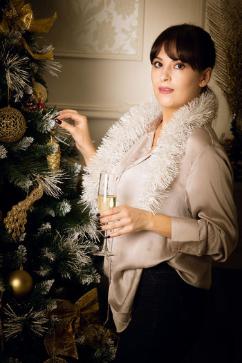 Portrait of young woman holding christmas tree