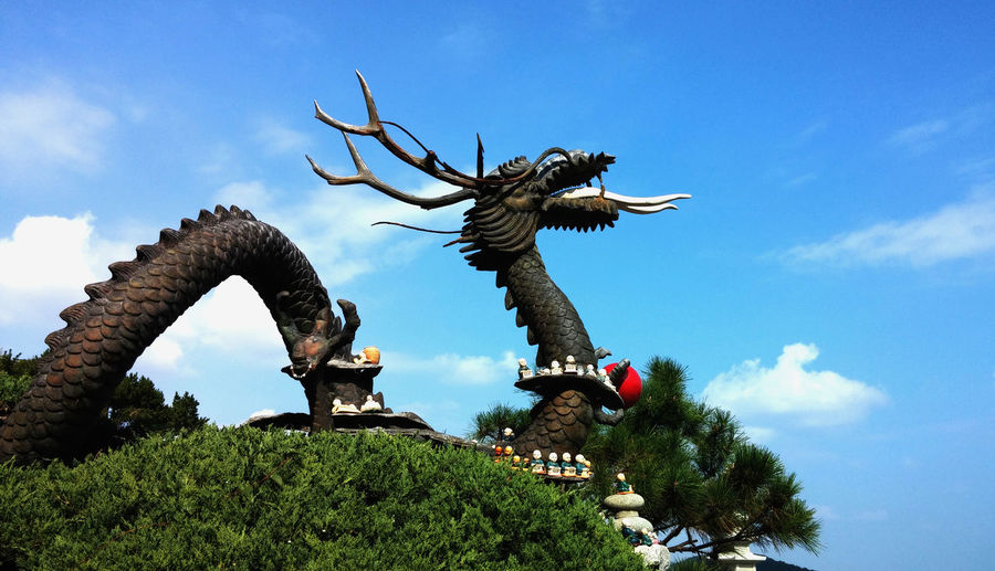 Dragon Statue Against Cloudy Sky