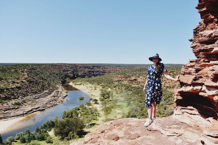 Woman standing on rock against clear blue sky