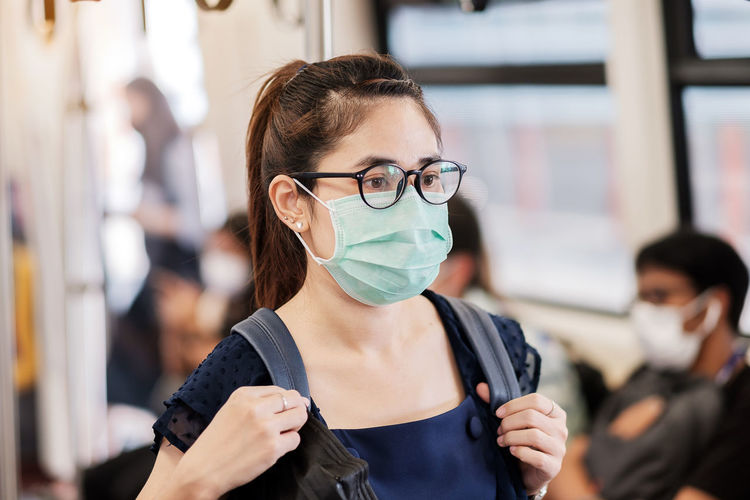 Close-up of woman wearing mask standing in train