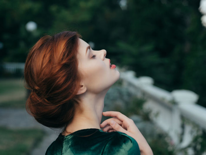 Portrait of a young woman looking up outdoors
