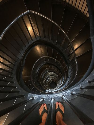 Low section of woman standing on spiral stairs