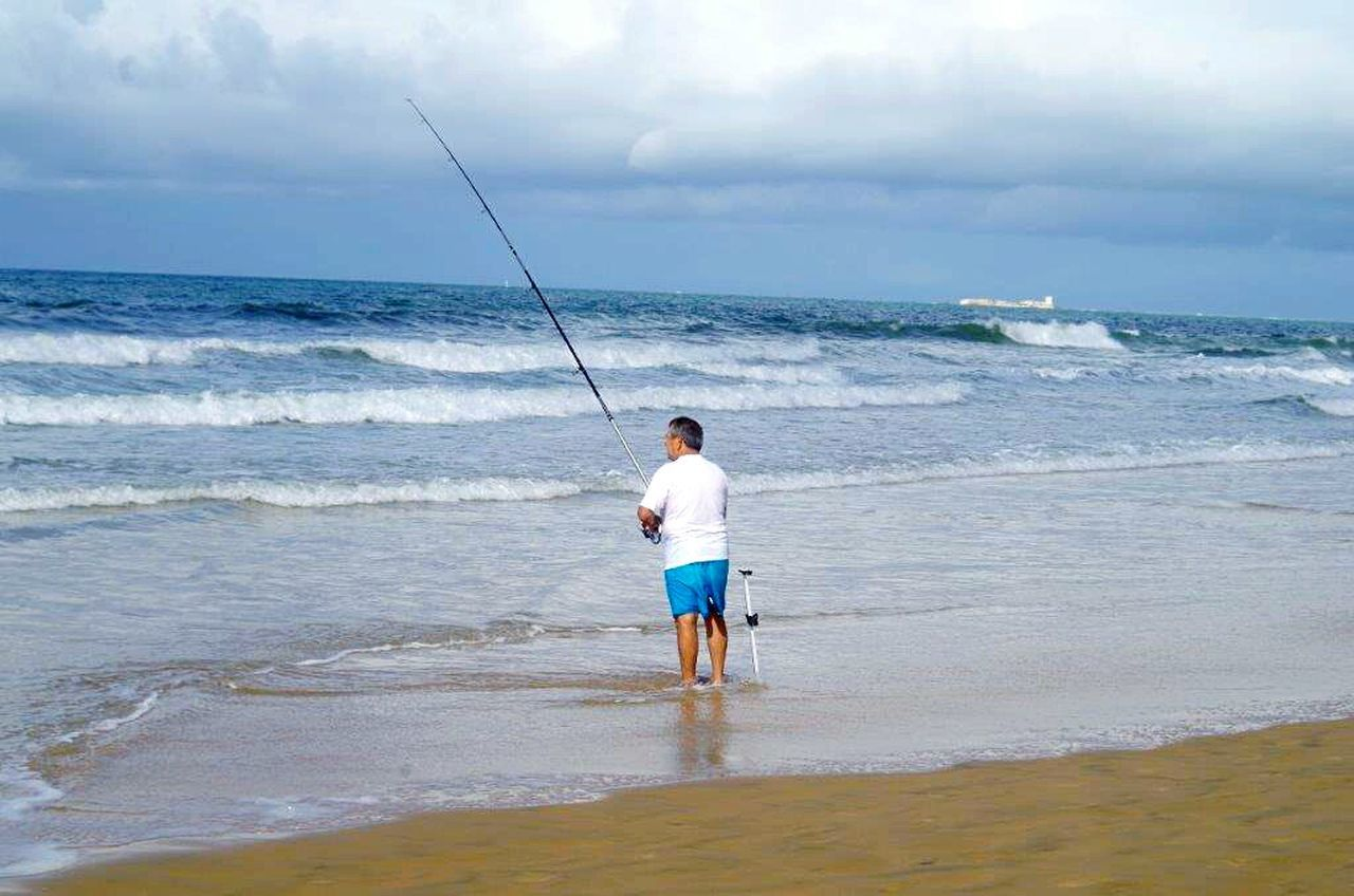 sea, horizon over water, rear view, real people, standing, nature, fishing, full length, water, one person, fishing pole, tranquil scene, beauty in nature, beach, leisure activity, men, weekend activities, sky, scenics, tranquility, day, holding, outdoors, cloud - sky, one man only, adult, people