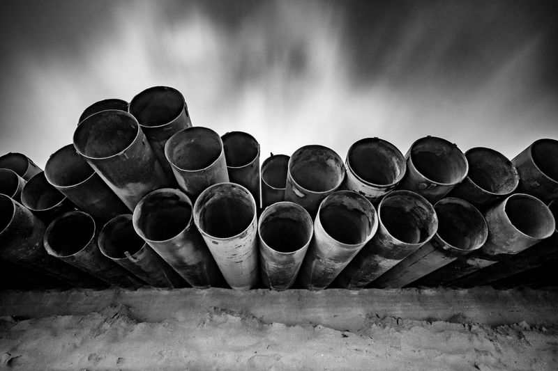 Low angle view of old pipes against sky