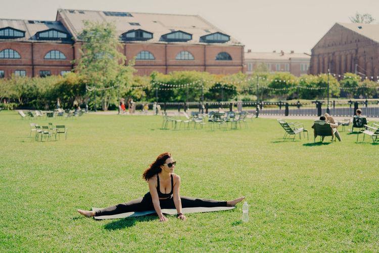 Full length of woman wearing sunglasses exercising on mat in park