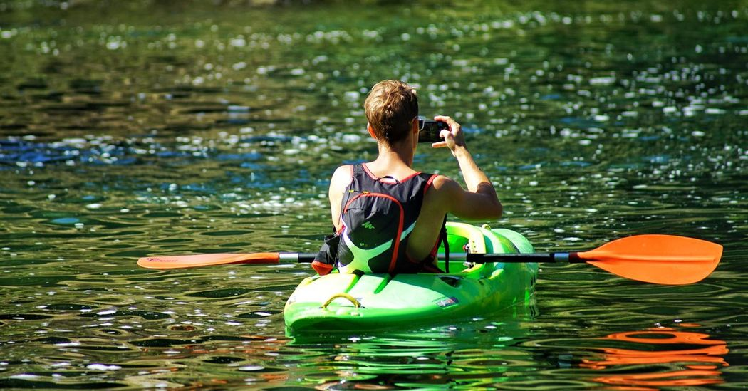 Taking a photo Oar Kayak Vacations Adventure Leisure Activity Sitting Exercising Life Jacket Recreational Pursuit Outdoors Water Paddleboarding Nature Day Healthy Lifestyle One Person Adult Sport Adults Only People