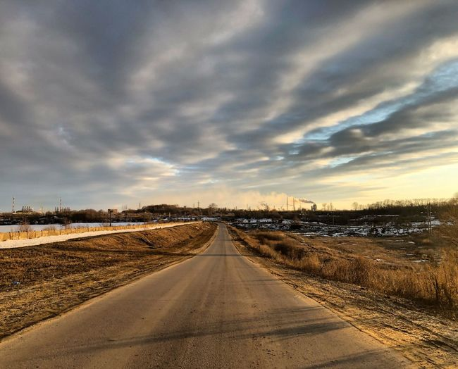 Empty road on field against sky at sunset