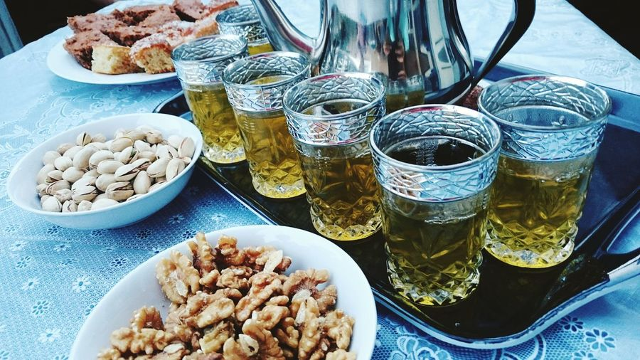 High angle view of beer glasses with nuts served on table