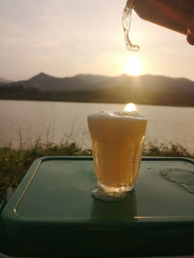 Close-up of drink by lake against sky during sunset