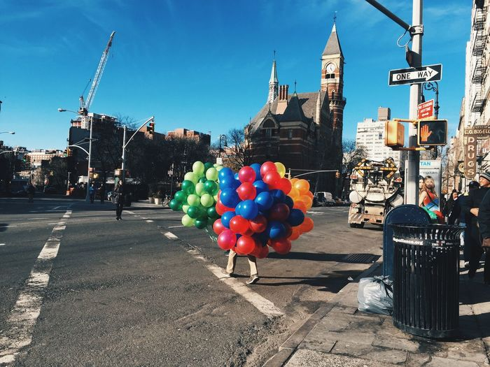 Man carrying bunch of colorful balloons on street