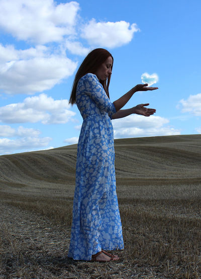 Full length of woman standing on field against sky