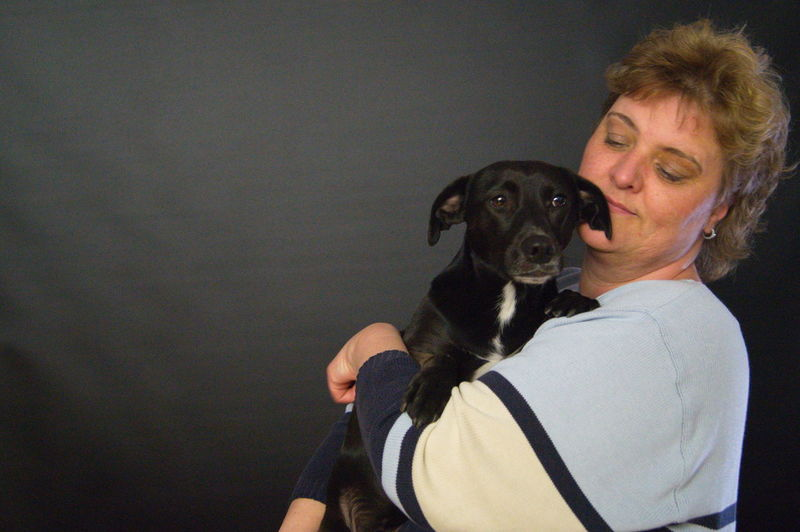 Mature woman holding puppy while standing against black curtain