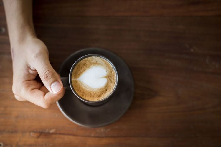 Cropped Image Of Hand Holding Cappuccino At Wooden Table