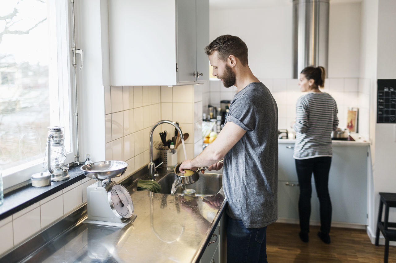 Man washing sauce pan while woman standing in background in kitchen