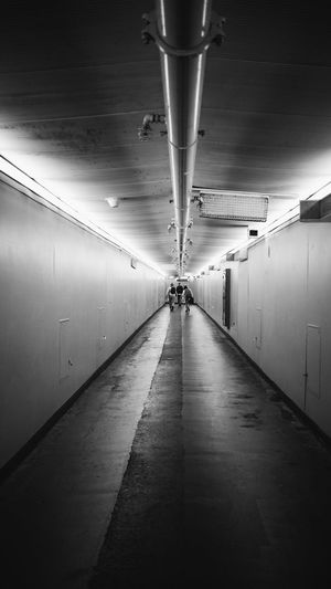Three People Far Away Three People In Distance Three People Walking Light Far Quiet Lonely Alone Backgrounds B&w Black And White Distance Walking Walk Three People Ceiling Indoors  The Way Forward Illuminated Lighting Equipment Built Structure Tunnel Architecture