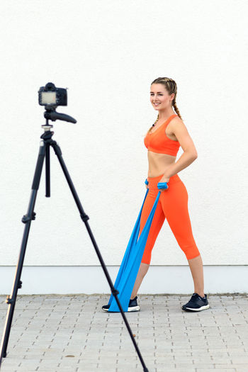 Female videoblogger making training exercises with a rubber band in front of a camera Blogger Camera Concept Exercise Female Fitness Full Length Health One Person Rubber Band Smiling Sports Summer Training Video Videoblogger Woman Workout