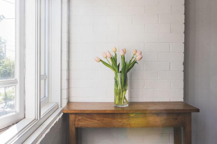 Flower vase against window at home